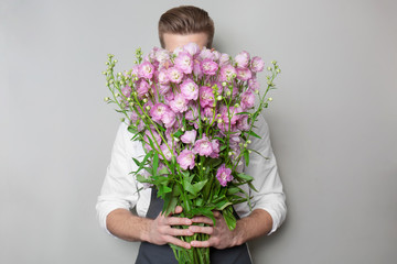 Young florist hiding behind beautiful bouquet on grey background