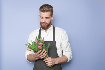 Young handsome florist with beautiful bouquet on blue background