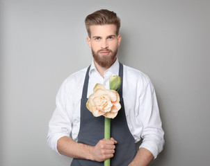 Young florist with beautiful flower on grey background