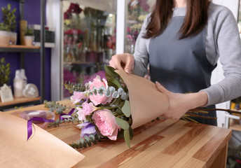 Female florist packing beautiful bouquet in wrapping paper at flower shop
