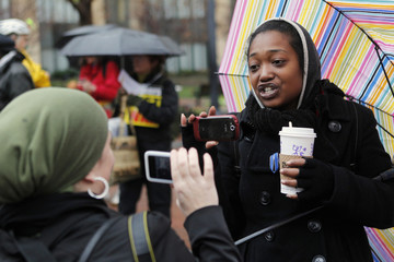 Hollie of Oakland, live video streams her conversation with another protestor, outside of the Ronald V. Dellums Federal Building Oakland