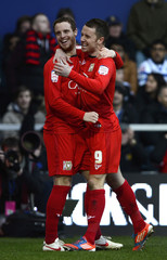 Milton Keynes Dons' Harley is congratulated by team mate Bowditch after scoring a goal past against Queens Park Rangers during their English FA Cup fourth round soccer match at Loftus Road in London