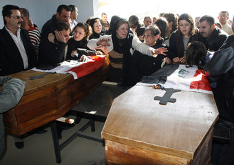 People grieve at the coffins of two Christian brothers killed on Monday, during their funeral, east of Mosul