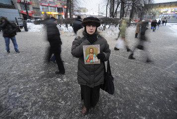 A woman holds a religious icon as she takes part in a rally to commemorate the victims of a bomb explosion at Domodedovo airport in central Moscow