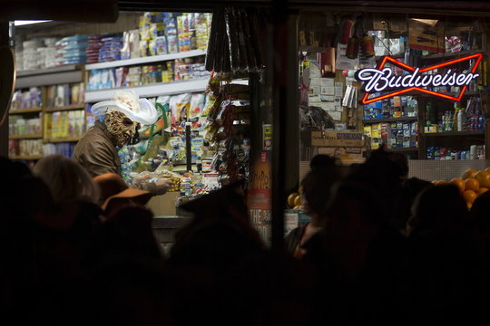 A man dressed as a monster with a cowboy hat makes a purchase at a bodega during the Greenwich Village Halloween Parade in Manhattan