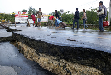 Commuters walk near the damaged portion of a highway in Loay, Bohol, after an earthquake struck central Philippines