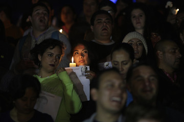 A woman holding a candle with a photograph of one of the missing 43 trainee teachers, stands during a protest at the Angel de la Independencia monument in Mexico City