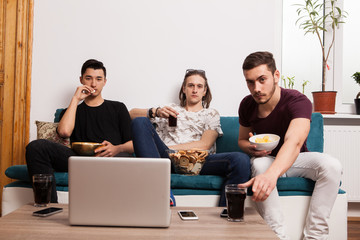 Friends watching a movie on laptop while eating snaks and drinking sodas. Spending time together. Male friendship