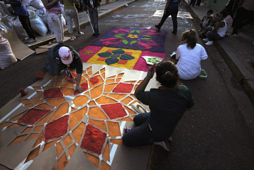 People use stencil paper to make a sawdust carpet in Tegucigalpa