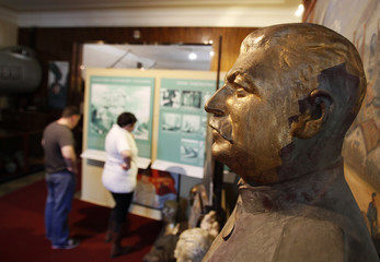 Visitors look at exhibits near a statue of former Soviet leader Joseph Stalin at the Museum of Communism in Prague