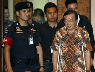 Teo is escorted by police officers before a news conference at the Royal Thai Police headquarters in Bangkok