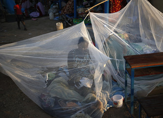 A woman sits inside a mosquito tent near a polling station located in a school during a referendum in the town of Abyei