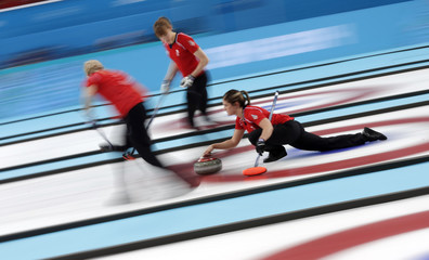 Britain's second Adams delivers a stone as vice Sloan and lead Hamilton prepare to sweep ahead of it during their women's curling bronze medal game against Switzerland at the 2014 Sochi Winter Olympics