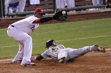 Giants' Torres dives back to the base as Phillies' Howard takes the throw during Game 6 of their MLB NLCS playoff series in Philadelphia