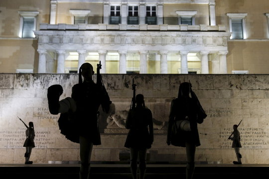 Greek Presidential guards are silhouetted as they conduct their ceremonial march in front of the Tomb of the Unknown Soldier in Athens