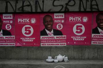 Posters of presidential candidate Jovenel Moise, of PHTK (Bald Head Haitian Party), are seen on a wall next to tea set on display for sale in a streett of Port-au-Prince, Haiti