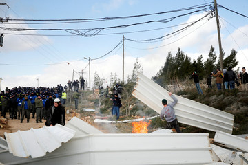 Pro-settlement activists set objects on fire as Israeli police stand nearby (L background) during an operation by Israeli forces to evict settlers from the illegal outpost of Amona in the occupied West Bank