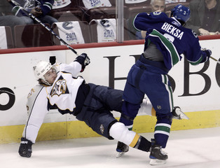 Predators center Fisher is hit into the boards by Canucks defenseman Bieksa in their NHL Western Conference semifinal hockey game