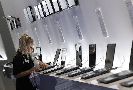 A woman wipes laptop computers before opening of IFA consumer electronics fair in Berlin