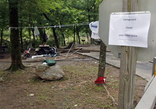 A sign announcing the closing of the campground is displayed amidst a clutter of personal items left behind at the Albert Pike recreation area near Caddo Gap