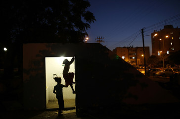 Israeli children play at the entrance to a public bomb shelter in Ashkelon