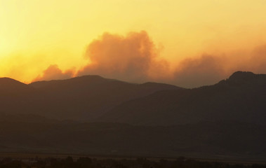 Smoke from the High Park fire rolls across the mountains at sunset, west of Fort Collins