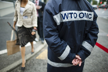 A security guard checks delegates arriving for Global Review of Aid for Trade at the WTO headquarters in Geneva