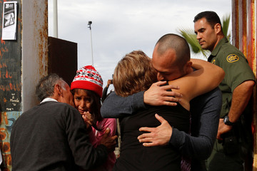 Relatives separated by immigration hug at an open gate on the fence along the Mexico and U.S border on Universal Children's Day in Tijuana