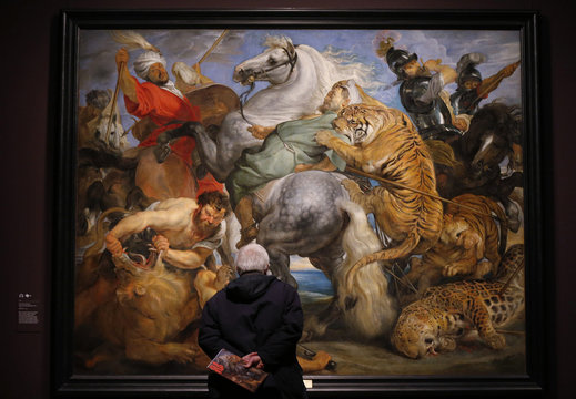 """A visitor looks at """"Tiger, Lion and Leopard Hunt"""" from 1617 by Peter Paul Rubens at an exhibition in London"""
