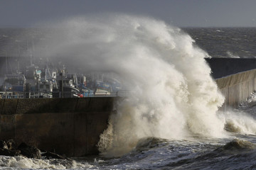A wave crashes into the Pornic harbour protecting wall as an autumn storm hits western France