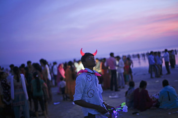 A man wearing devil horn as he sells toys on a beach along the Arabian Sea in Mumbai