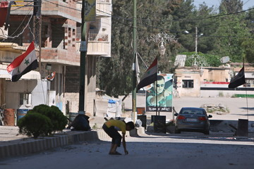 A boy collects empty bullet casings as Syrian national flags and a picture of Syria's President Bashar al-Assad are seen in the city of Qamishli