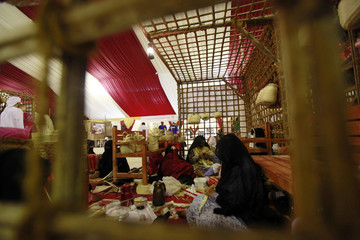 Women weave saaf (khoos) stems taken from Palm trees to make handmade baskets for arranging dates during the eighth round of the Liwa Date Festival, in the western Region of Liwa in the United Arab Emirates