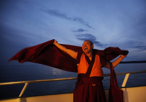 """A Buddhist monk laughs during the release of lobsters back into the ocean on """"Chokhor Duchen"""" in the waters off Gloucester"""