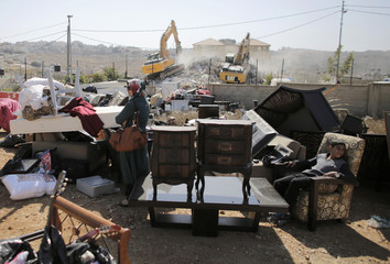 A Palestinian woman stands near furniture removed from her house as it is being demolished in East Jerusalem