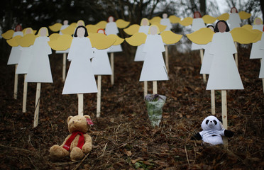 Stuffed animals left by mourners sit beneath some of the 27 wooden angel figures placed in a wooded area beside a road near the Sandy Hook Elementary School for the victims of a school shooting in Newtown