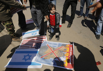 A Palestinian girl stands near a picture of U.S. President Obama and American and Israeli flags on ground during a protest against Obama's visit, in Gaza