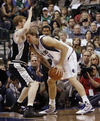 Spurs forward Bonner defends Mavericks forward Nowitzki during Game 1 of NBA Western Conference series in Dallas