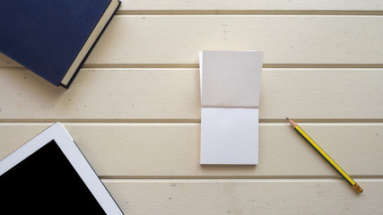 Wall Mural - top view with notebook  and pencil on wood background