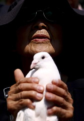 Woman holds a dove as symbol of peace at Yasukuni Shrine on the anniversary of Japan's surrender in World War Two in Tokyo