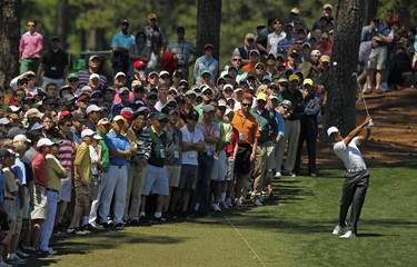Woods of the U.S. hits his approach shot to the ninth green from the first fairway after an errant tee shot during third round play in the 2012 Masters Golf Tournament in Augusta