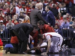 Louisville Cardinals head coach Rick Pitino and guard Luke Hancock console guard Kevin Ware