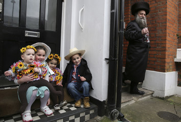 A Jewish family dressed in colourful costumes celebrate the festival of Purim in Stamford Hill in north London