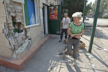 Local residents stand near their shop which was damaged in fights between the Ukrainian army and pro-Russian separatists in Vuhlehirsk