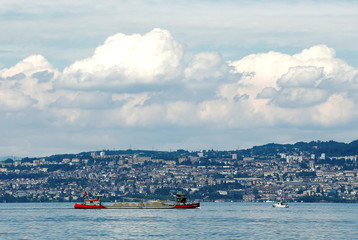 A barge carrying gravel sails on Lake Leman with Lausanne, Switzerland in the background, in Evian-les-Bains