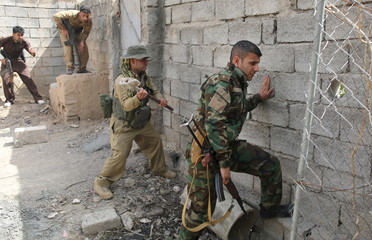 A Kurdish gunman uses a hammer to open a hole in a wall near Shi'ite militiamen positions during clashes Tuz Khurmato