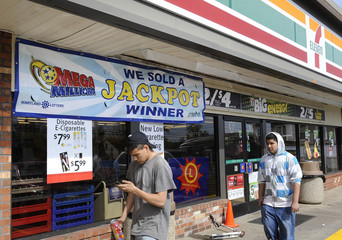 People walk outside the 7-Eleven store where a potential winning ticket for the Mega Millions jackpot lottery was sold last week in Baltimore County