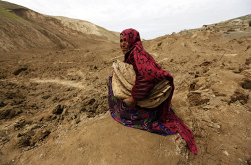 An Afghan woman cries after she lost her family in a landslide at the Argo district in Badakhshan province