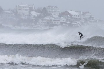 Surfers take advantage of wind and waves from a winter snow storm in Gloucester