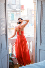 Young beautiful woman in red dress on old balcony in apartment in Old Havana, Cuba.